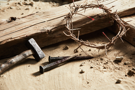 Easter background depicting the crucifixion with a rustic wooden cross, hammer, nails and crown of thorns in a close up cropped view on sand
