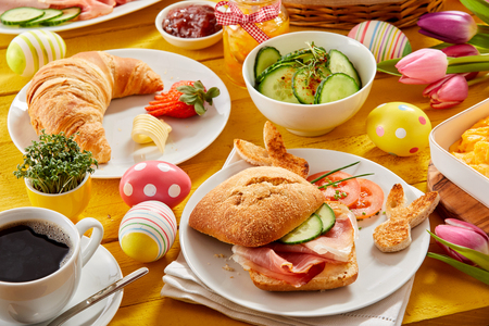 Photo pour Tasty Easter brunch or spring breakfast with a fresh croissant, ham or bacon roll and coffee on a table decorated with colorful Easter eggs and tulips - image libre de droit