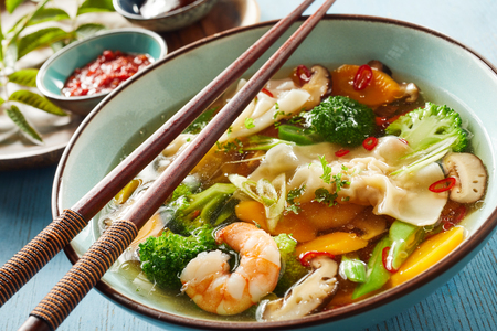 Delicious health Asian wonton soup with dough dumplings, fresh vegetables and shrimp or prawn in a close up view on the bowl with chopsticks