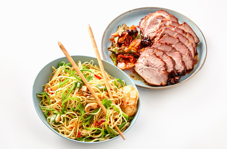 High Angle Close Up Still Life of Vegetarian Asian Chinese Noodle Dish in Large Bowl with Chopsticks Beside Plate of Roast and Sliced Pork on White Background
