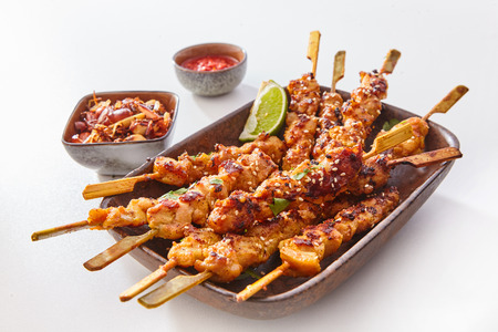 Foto de Close Up Still Life of Dish of Grilled Pork or Chicken on Wooden Skewers with Lime Garnish and Sauce on White Studio Background - Imagen libre de derechos