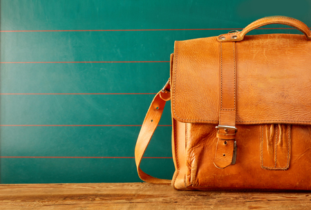 Foto de Closed leather backpack case with copy space over green wall and old wooden table - Imagen libre de derechos