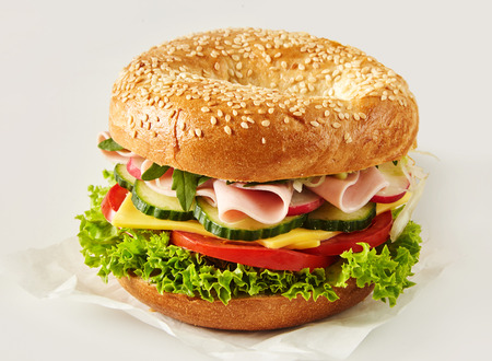 Foto de Crusty sesame bun or bagel with ham, cheese and salad filling on paper over white for advertising or a menu - Imagen libre de derechos