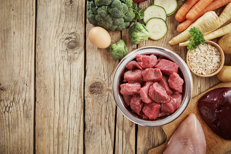 Foto de Fresh ingredients for a healthy nutritious dog diet with a bowl of chopped raw beef, chicken, liver, egg. assorted vegetables and grains in an overhead view on wood with copy space - Imagen libre de derechos