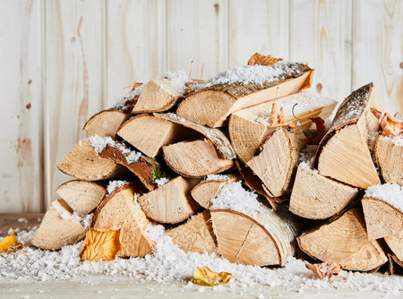 Photo for Small woodpile of dried logs in winter snow with scattered autumn leaves against a rustic white painted wooden wall - Royalty Free Image