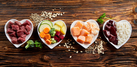 Photo for Panorama banner of healthy fresh ingredients for pet food in individual heart-shaped bowls viewed from overhead with chopped raw beef, liver and chicken , mixed vegetables and rains on rustic wood - Royalty Free Image