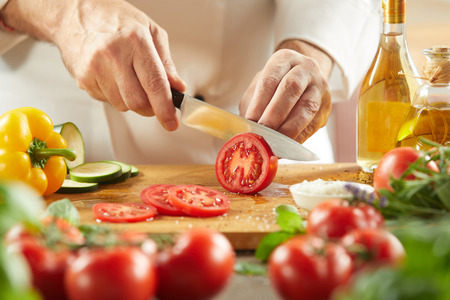 Photo pour Chef preparing a fresh Italian or Mediterranean salad slicing a fresh tomato on a cutting board surrounded by vegetables, herbs, and olive oil, close up on hands - image libre de droit