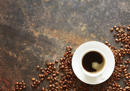 Photo pour cup of freshly brewed espresso coffee with roasted beans arranged in the corner on textured slate with advertising for advertising or a menu - image libre de droit