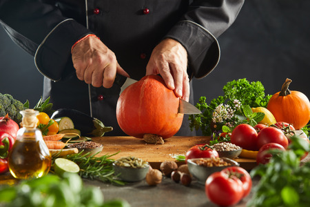 Photo pour Restaurant worker in black suit cutting open small orange pumpkin sitting on wooden cutting board surrounded by vegetables - image libre de droit