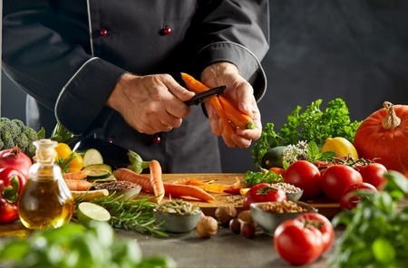 Foto de Man in black chef outfit peeling carrot over wooden cutting board sitting on top of dark table and misty darkness in background - Imagen libre de derechos