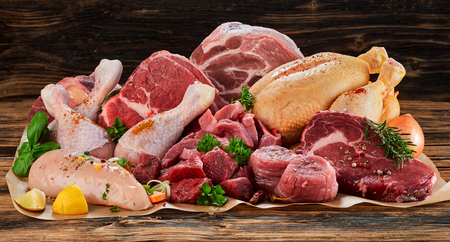 Foto de Raw meat assortment, beef, chicken, turkey, decorated with greens and vegetables, placed on cooking paper on wooden table - Imagen libre de derechos