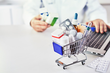 Foto de Close-up of various medicines in a small shopping cart on the desk of a drugstore with electronic payment as concept for costs and healthcare - Imagen libre de derechos