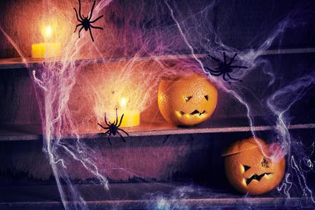 Photo pour Spooky Halloween jack-o-lanterns and spiders entwined with spider webs on old wooden shelves with candles glowing in the shadows - image libre de droit