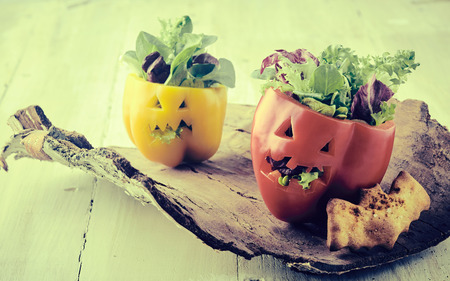 Photo pour Rustic vintage Halloween food table decorations with carved faces on fresh bell peppers stuffed with salad with faded effect - image libre de droit