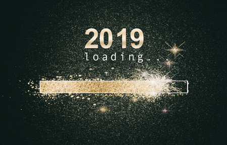 Foto de Glittering New Years background with a loading computer screen with sparkling gold bar and date over a black background - Imagen libre de derechos