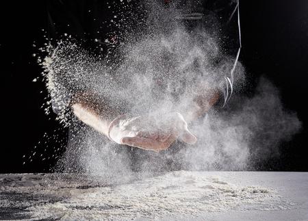 Foto de Restaurant worker in black suit and latex gloves wiping white powdery flour off hands onto rectangular - Imagen libre de derechos