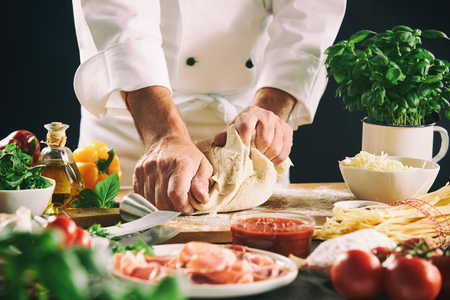 Photo pour Chef kneading pastry dough for pasta or pizza in a close up view of his hands and assorted fresh ingredients - image libre de droit