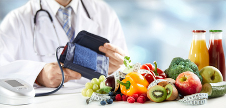 Photo pour Healthy diet and blood pressure concept with an assortment of colorful fresh fruit, vegetables and smoothies in front of the hands of a doctor holding a sphygmomanometer or cuff in a panorama banner - image libre de droit