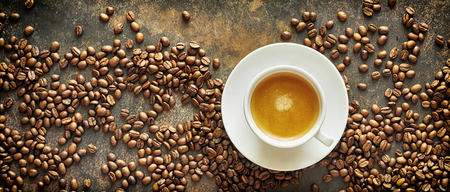 Photo pour Panorama banner with roasted coffee beans and a generic white cup and saucer of milky latte coffee on a textured slate background viewed from above - image libre de droit