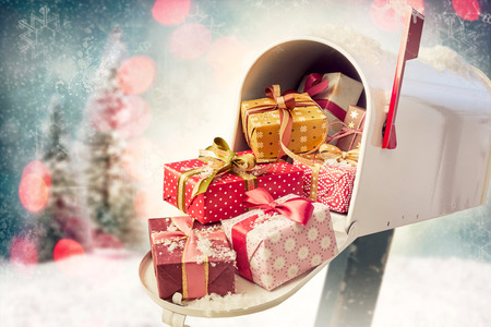 Foto de Holiday presents in the open full mailbox with Christmas decorations background. Concept of sending gifts by mail in holiday season with copy space - Imagen libre de derechos