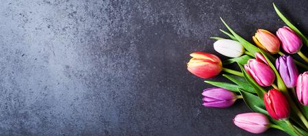 Foto de Bouquet of fresh colorful tulip flowers sitting on dark surface background with copy space - Imagen libre de derechos