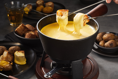 Foto de Delicious cheese fondue with dipping forks coated in melted cheese surrounded by assorted breads and potatoes - Imagen libre de derechos