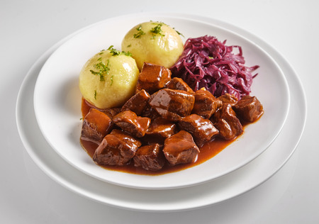 Wild boar and deer hot pot or goulash with diced meat in a rich sauce served with dumplings and shredded red cabbage on a white plate