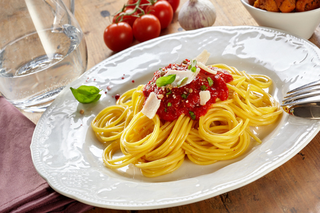 Foto de Plate of spaghetti Bolognaise or Bolognese with a tomato and herb topping sprinkled wth parmesan cheese in a tilted view on a wooden table - Imagen libre de derechos