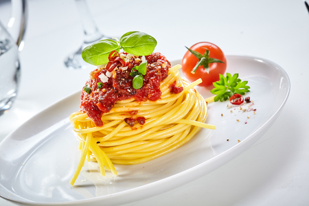 Foto de Spaghetti Bolognaise with tomato topping sprinkled with parmesan cheese and spices and garnished with basil served with a fresh tomato on a tilted white plate - Imagen libre de derechos