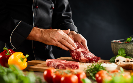 Foto de Chef seasoning a thick raw beef steak with spice rub on a wooden board with fresh vegetables and herbs in a close up of the hands - Imagen libre de derechos