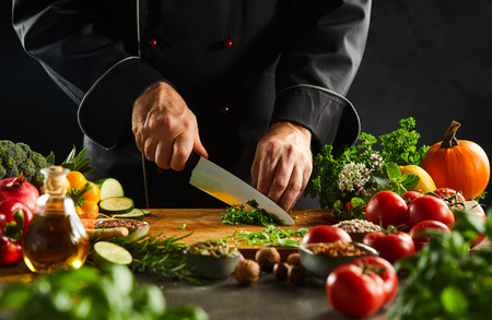 Foto de Chef dicing fresh herbs on a wooden chopping board with a kitchen knife while preparing salad in a close up on the hands - Imagen libre de derechos