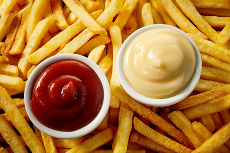 Two individual bowls of tomato sauce and mayonnaise on top of a background of crispy french fries