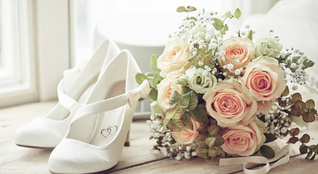 Foto de Bridal bouquet, pair of white shoes decorated with hearts and white hat. Wedding composition sitting on window sill in bright light, viewed in close-up - Imagen libre de derechos