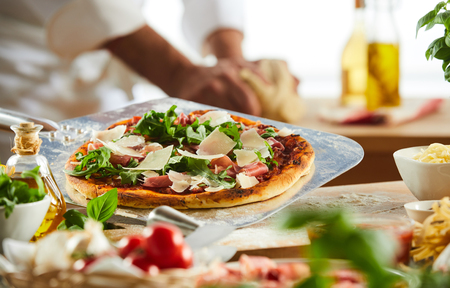 Foto de Metal pizzeria paddle with crusty Italian pizza topped with rocket, ham and cheese with foreground ingredients - Imagen libre de derechos