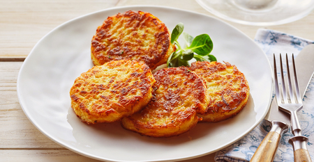 Photo pour Plate of crispy golden fried potato fritters with watercress, a traditional German and Bavarian dish - image libre de droit