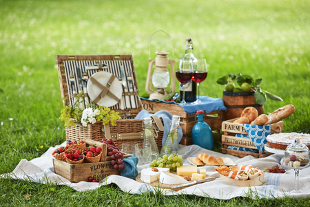 Foto de Wicker picnic hamper with assorted fresh food, infused water and wine on a rug spread out on the green grass in a park - Imagen libre de derechos