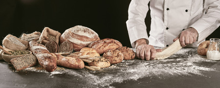 Baker kneading raw dough while making assorted speciality bread displayed alongside on a floured counter in panorama banner format