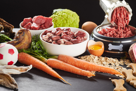 Foto de Preparing raw barf food for a pet dog or cat mincing offal - Imagen libre de derechos