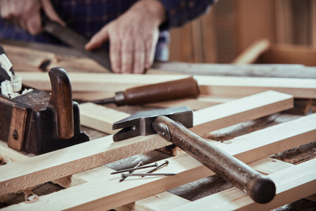 Photo pour Carpenter working in his workshop with freshly planed planks with old hand tools and nails in the foreground - image libre de droit