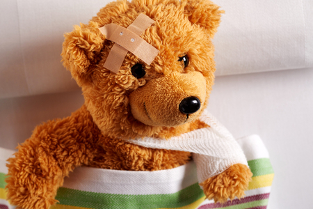 Foto de Injured teddy bear with bandaged arm and head lying in bed after an accident in a closeup view in a concept of paediatric medicine for kids - Imagen libre de derechos