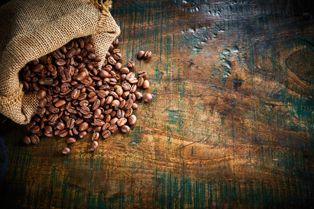 Photo pour Small hessian bag of fresh roasted coffee beans spilling onto an old rustic wood surface with copy space viewed from above - image libre de droit