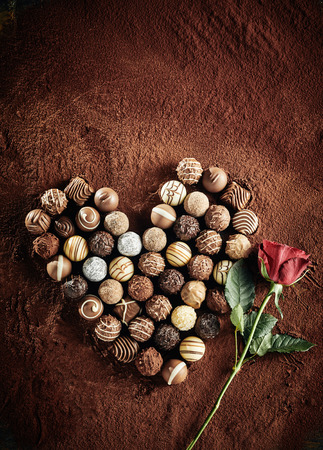 Foto de Heart shaped still life of an assorted selection luxury chocolate bonbons on a bed of cocoa powder with a red rose symbolic of love ad romance with copy space above for valentines greeting - Imagen libre de derechos