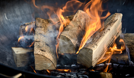 Photo pour Recently lit fire with logs of flaming wood on a bed of chopped kindling in a portable summer barbecue in a close up panorama banner view - image libre de droit