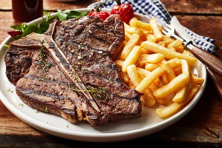 Foto de Tasty grilled T-bone steak seasoned with herbs and spices served with deep fried potato chips and salad in a close up view for menu advertising - Imagen libre de derechos