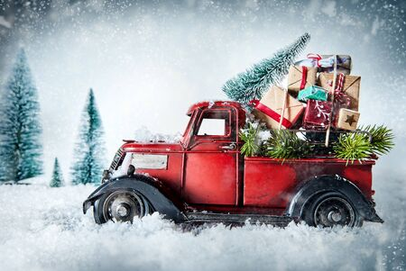Foto de Festive red vintage truck laden with Christmas gifts and pine tree for decorating driving through a winter snow storm in a greeting card design with copy space - Imagen libre de derechos