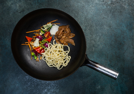 Asian Wok - Traditional oriental pan with raw ingredients on a vintage colored background. Top view