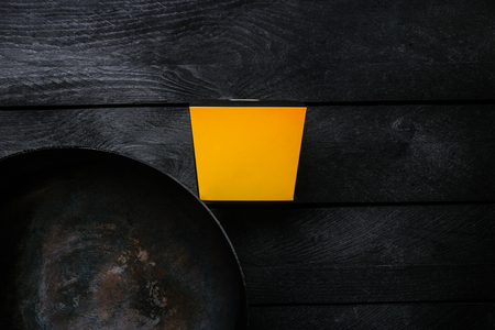 Asian Wok - Traditional oriental pan on a black wooden background. With a box for noodles. Top view