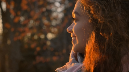 Close-up portrait in profile of curly-haired caucasian girl watching sidewards joyfully in autumnal park.