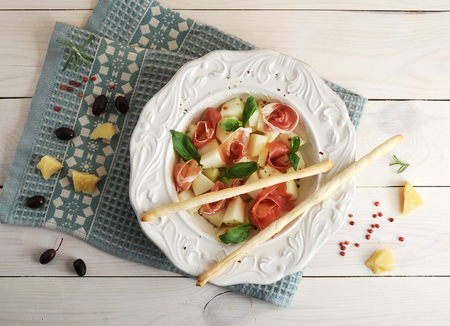 ham with melon and breadsticks on a plate, olives and Parmesan cheese on wooden background - top viewの写真素材