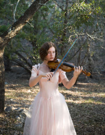 A pretty young woman/teenager in a vintage dress holding a violin and bow in a woodland setting. Subject is backlit, and photo has a nostalgic feel. Plenty of background at top of picture for type, etc.